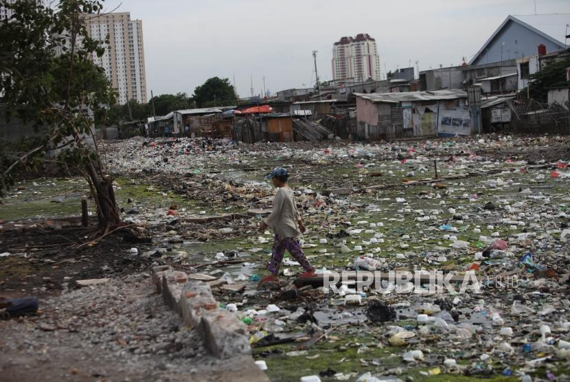 Resident crosses among the piles of garbage in the residential area Muara Baru area, Jakarta, December, 28, 2017.