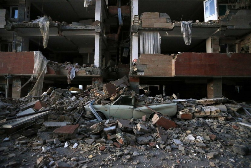 A car lays smashed by debris from the earthquake at the city of Sarpol-e-Zahab in western Iran, Monday, Nov. 13, 2017. A powerful earthquake shook the Iran-Iraq border late Sunday, killing more than two hundred people and injuring some 800 in the mountainous region of Iran alone, state media there said.