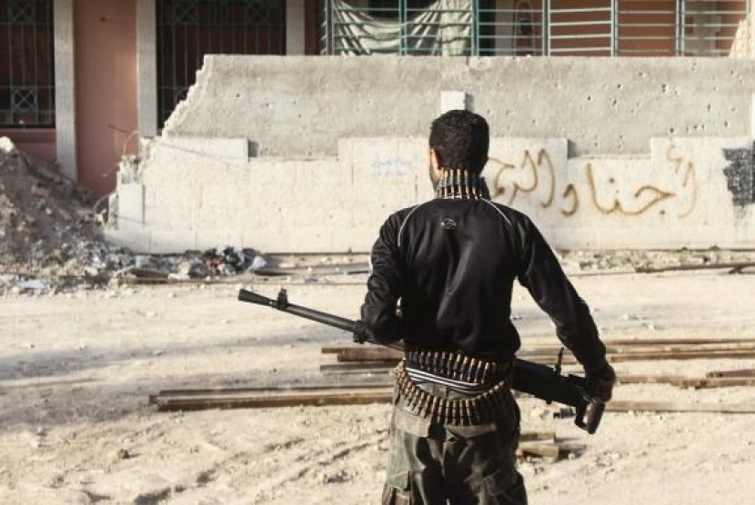 A Free Syrian Army fighter carries his weapon on one of the battlefronts in Jobar, a suburb of Damascus February 22, 2014.