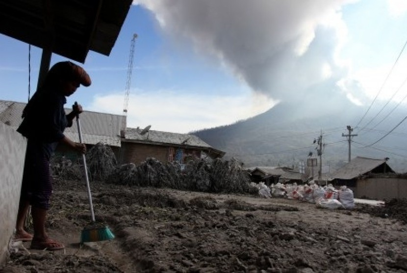 A resident cleans her house from Mount Sinabung's volcanic ash in Karo, North Sumatra, last week. (File photo)