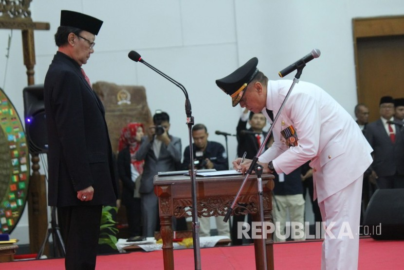 Home Affairs Minister Tjahjo Kumolo (left) witnesses Commissioner General Mochamad Iriawan signs a decree of his appointment as acting governor of West Java at Merdeka Building, Bandung, West Java, on Monday (June 18).