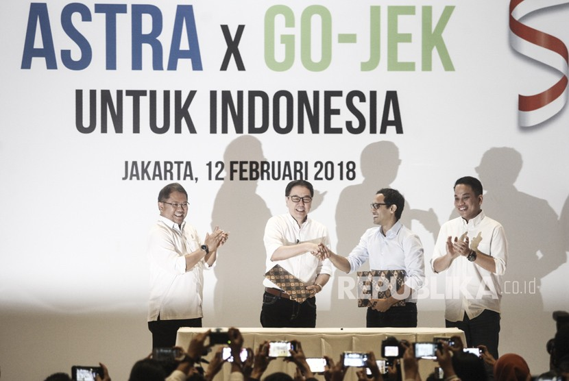 Minister of Communication and Informatics Rudiantara (left) with Gojek President Andre Soelistyo (right) witness the signing of an investment agreement between Astra International and Gojek conducted by PT Astra International Tbk President Director Prijono Sugiarto (second left) and CEO & Co-founder of Gojek Nadiem Makariem (second right) in Jakarta, Monday (Feb 12).
