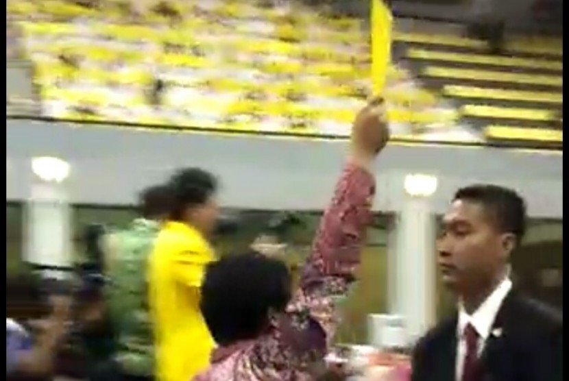 A student activist gives President Joko Widodo a yellow card at the 68th anniversary of University of Indonesia, Depok, West Java, on Friday (Feb 2).