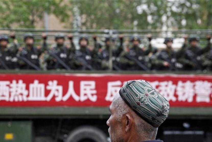 An Uighur Muslim passes in front of Chinese military patrols in Xinjiang.