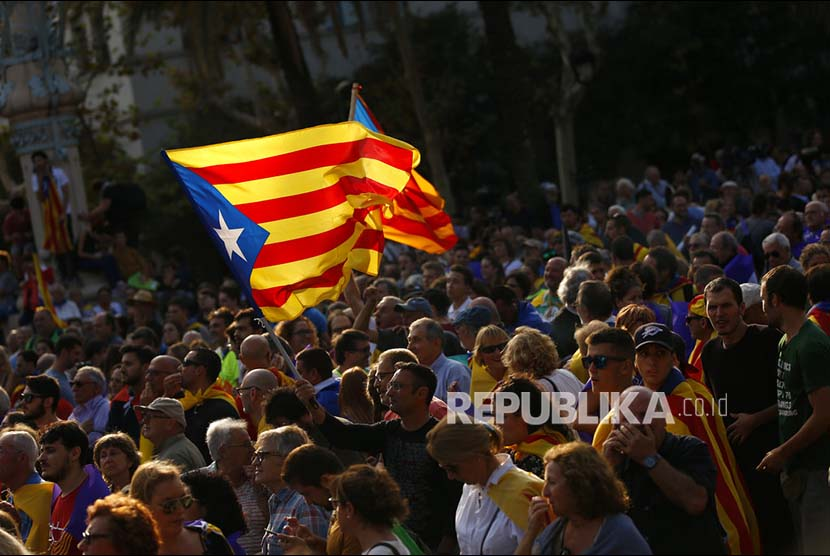 Demonstrators wave Catalan flag during a rally in Barcelona.